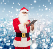 Homem no traje de Papai Noel com PC da tabuleta Foto de Stock