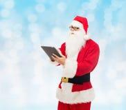 Homem no traje de Papai Noel com PC da tabuleta Imagem de Stock