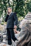 Homem no traje escuro reto que introduz seu dinheiro no copo usado do cartão foto de stock royalty free