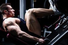 Homem no treinamento do gym na imprensa do pé fotografia de stock royalty free