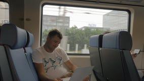 Homem no trem que diverte o portátil vídeos de arquivo
