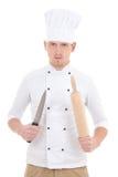 Homem no uniforme do cozinheiro chefe com iso de madeira do pino e da faca do rolo do cozimento Imagens de Stock