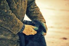 Homem no uniforme militar que afaga um c?o o homem mostra a pena e o interesse para animais desabrigados imagens de stock
