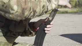 Homem no uniforme militar que carrega as bolas na máquina do airsoft da gaiola Compartimentos da arma de Airsoft video estoque