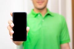 Homem no verde que mantém a zombaria móvel preta da tela imagem de stock royalty free