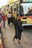 Homem no vestido tradicional que anda nas ruas movimentadas de Yangon, Foto de Stock Royalty Free