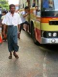 Homem no vestido tradicional que anda nas ruas movimentadas de Yangon, Imagem de Stock