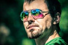 Homem nos óculos de sol com reflexão colorida Foto de Stock