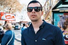 Homem nos óculos de sol que estão na estação de ônibus imagem de stock