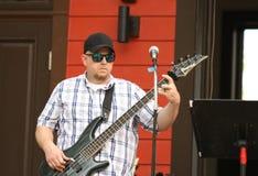 Homem nos óculos de sol que jogam o baixo durante um concerto exterior Imagens de Stock