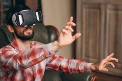 Homem nos auriculares da realidade virtual que jogam o jogo de vídeo fotos de stock royalty free