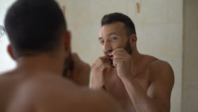 Homem nos dentes das escovas do banheiro com fio dental, prevenção das doenças do dente filme