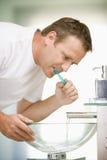 Homem nos dentes de escovadela do banheiro foto de stock royalty free