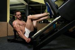 Homem nos pés do exercício da imprensa do pé fotos de stock royalty free