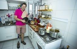 Homem nos pratos de lavagem da cozinha foto de stock royalty free