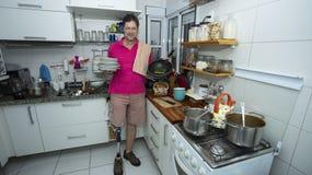 Homem nos pratos de lavagem da cozinha fotografia de stock