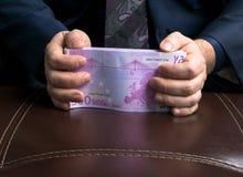 Homem nos ternos dos homens Subôrno e corrupção com euro- cédulas Homem que guarda um pacote de euro- dinheiro Foto de Stock