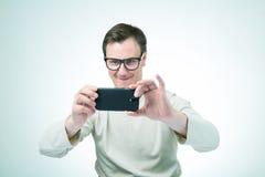Homem nos vidros fotografados pelo smartphone Fotos de Stock