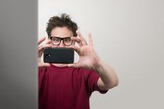 Homem nos vidros fotografados pelo smartphone Fotografia de Stock