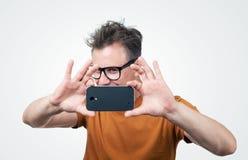 Homem nos vidros fotografados pelo smartphone Imagens de Stock Royalty Free