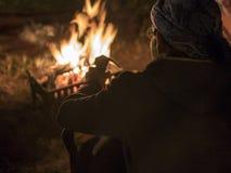 Homem nos vidros perto da fogueira na noite no castelo velho de Uchisar da cidade da caverna em Cappadocia imagens de stock