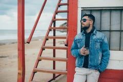 Homem novo à moda com uma barba que está o oceano próximo com um copo do chá Fotografia de Stock Royalty Free