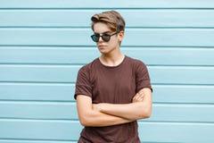 Homem novo à moda do moderno com um penteado elegante em óculos de sol escuros em um t-shirt marrom na moda que levanta perto de  fotos de stock royalty free