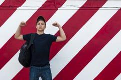 Homem novo à moda em um fundo brilhante da parede Fotos de Stock