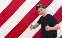 Homem novo à moda em um fundo brilhante da parede Imagem de Stock Royalty Free