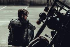 Homem novo à moda no casaco de cabedal que senta-se perto do velomotor e que olha afastado Fotos de Stock Royalty Free