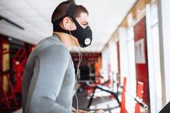 Homem novo acima bombeado bonito, contratado nos esportes, na máscara do treinamento para respirar na escada rolante, treinamento fotografia de stock royalty free