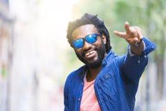 Homem novo africano considerável que faz Victory Sign foto de stock