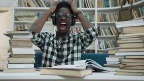 Homem novo africano fatigante que estudam no fones de ouvido e começo que grita na biblioteca à moda filme