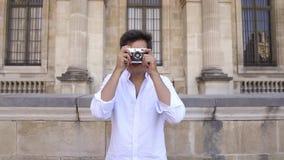 Homem novo alegre com cabelo escuro na camisa que toma fotos Tiro do retrato do movimento lento video estoque