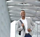 Homem novo alegre que anda no aeroporto com saco Fotos de Stock