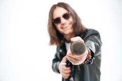 Homem novo alegre que dá o microfone e que oferece o cantar imagem de stock