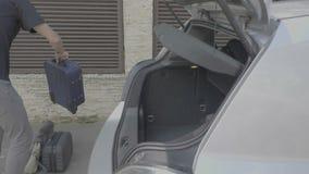 Homem novo alegre que decola a bagagem do tronco do carro estacionado que chega no conceito do curso de carro do destino - filme