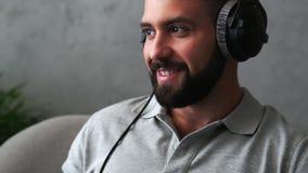 Homem novo alegre que escuta sua música favorita vídeos de arquivo
