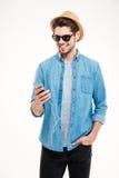 Homem novo alegre que está e que usa o smartphone Fotos de Stock Royalty Free