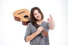 Homem novo alegre que guarda a guitarra e que faz o gesto da rocha Imagem de Stock Royalty Free