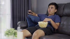 Homem novo alegre que guarda a tevê de controle remoto e olhando ao sentar-se no sofá vídeos de arquivo