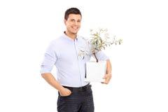 Homem novo alegre que guarda um vaso de flores Imagens de Stock