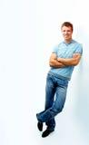 Homem novo alegre que inclina-se de encontro à parede Fotografia de Stock
