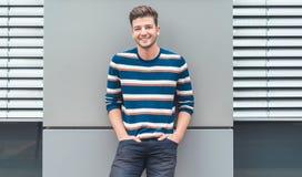Homem novo alegre que olha a câmera, indivíduo feliz que inclina-se à parede cinzenta imagens de stock