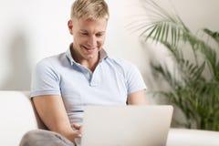 Homem novo alegre que senta-se no sofá com portátil. imagem de stock royalty free