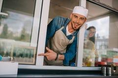 homem novo alegre que sorri na câmera e que aponta com o dedo no sinal aberto imagens de stock