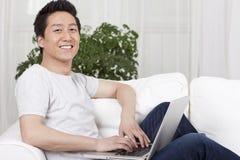 Homem novo alegre que usa um portátil no sofá Fotos de Stock Royalty Free
