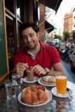 Homem novo andaluz considerável que come o pequeno almoço fotografia de stock royalty free