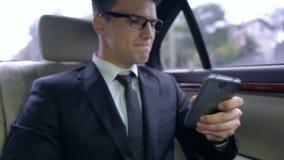 Homem novo ansioso no terno que recebe a mensagem com más notícias, passeio no automóvel luxuoso video estoque