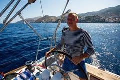 Homem novo ao leme de um barco do iate da navigação esporte fotos de stock royalty free